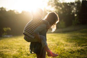 公園で遊ぶ姉弟と夕日