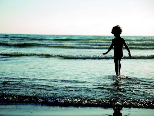海に立つ男の子のシルエット