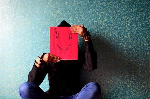 笑顔のイラストで顔を隠している男